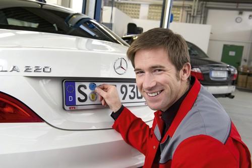 Ein GTÜ-Prüfingenieur bringt eine HU-Plakette an.  Foto: Auto-Medienportal.Net/GTÜ/KD Busch